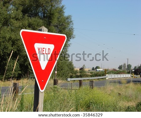 Yield sign along old country road - stock photo