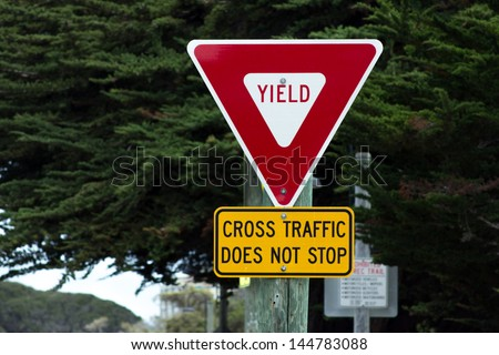 Yield Sign Cross Traffic Does Not Stop Road Sign - stock photo