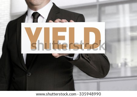 yield sign held by businessman concept. - stock photo