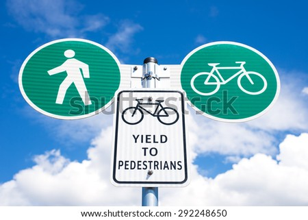 yield to pedestrians road sign on a sunny day with white clouds behind. pedestrian and bicycle crossing symbols on green background and side by side. horizontal, close up. - stock photo