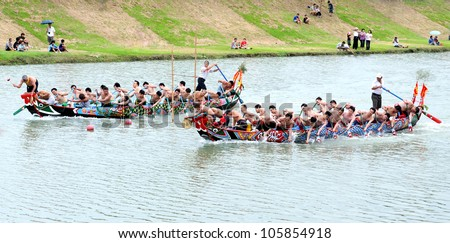 YILAN TAIWAN - JUNE 23:  Both sides of dragon boats start accelerate. Erlong Dragon boat racing festival on the Erlong River on June 23, 2012 in Yilan - stock photo