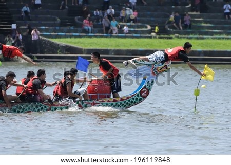 YILAN TAIWAN - JUNE 1: yellow team's flag fetcher first snatched the flag at the end point. The Dragon Boat Festival on the Dongshan River on June 1, 2014 in Yilan - stock photo