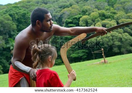 Yirrganydji Aboriginal warrior teaches a little girl how to throw a boomerang during cultural show in Queensland, Australia. - stock photo