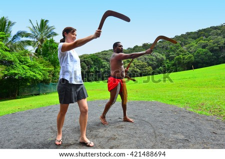 Yirrganydji Aboriginal warrior teaches a young woman how to throw a boomerang during cultural show in Queensland, Australia. - stock photo