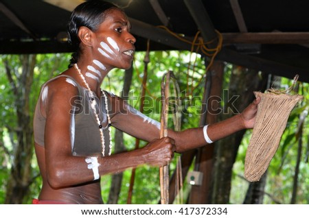 Yirrganydji Aboriginal woman explain about the home tools made by the indigenous Australian people of Queensland, Australia. - stock photo