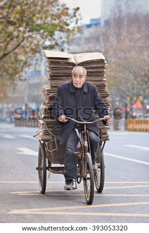 YIWU-CHINA-JAN. 8, 2016. Senior man transports cardboard on a tricycle. Elderly population of China (60 or older) is currently about 128 million, one in every ten people, the largest in the world.  - stock photo