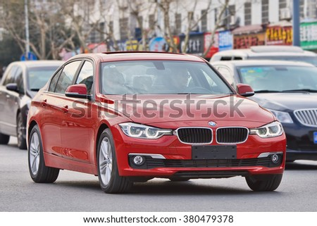 YIWU-CHINA-JANUARY 26, 2016. BMW 3 series on the road. BMW sales will be hit in 2016 by cut-throat competition, slowing Chinese economy and government crackdown on graft and conspicuous consumption. - stock photo