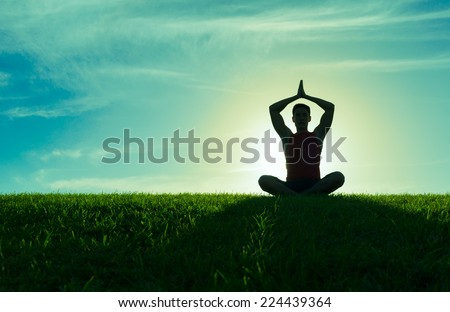 Yoga and fitness. Silhouette of man meditating - stock photo