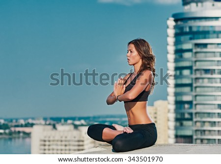 Yoga and meditation in a modern urbanistic city. Young attractive girl - yoga meditates against modern skyscrapers