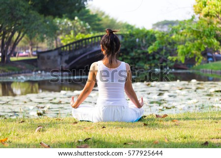 Yoga and meditation of woman with white clothes in park and green grass background.
