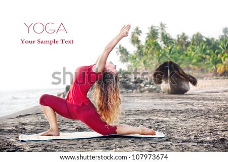Yoga Ashva Sanchalanasana pose by young woman with long hair in red cloth on the beach near the ocean at palm tree and boat background. Free space for your text - stock photo