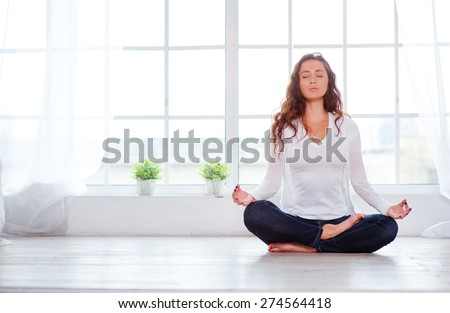 Yoga at home. Keep calm. Attractive young woman sitting on lotus position on floor with eyes closed. - stock photo
