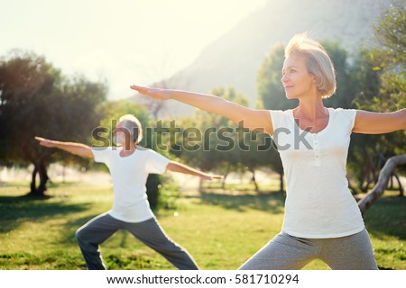 Yoga at park. Senior family couple exercising outdoors. Concept of healthy lifestyle.