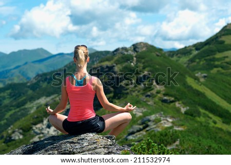 Yoga at summit with aerial view of the mountain range and peak. Blue sky.