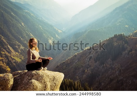 Yoga at summit with aerial view of the mountain range and peak. Blue sky. - stock photo