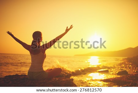 yoga at sunset on the beach. woman doing yoga, performing asanas and enjoying life on the sea - stock photo
