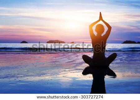 yoga background, abstract silhouette of woman meditating on the beach - stock photo
