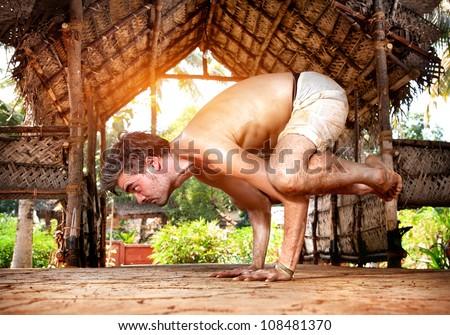 Yoga bakasana crane pose by fit man in white trousers on the drought earth in yoga shala, Varkala, Kerala, India - stock photo