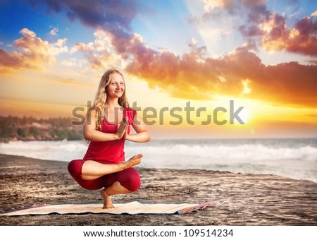 Yoga balancing pose by young woman with long hair in red cloth on the beach near the ocean at dramatic sunset background - stock photo