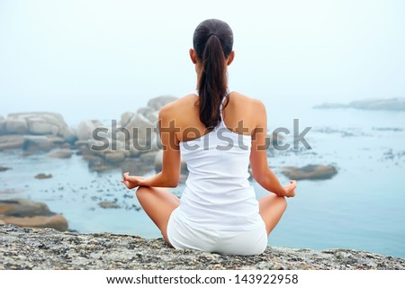 yoga beach woman doing pose at the ocean for zen health and peaceful lifestyle - stock photo