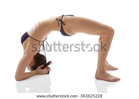 Yoga. Bridge exercise. Asana. Yoga pose. Beautiful woman in 20s in bikini doing bridge exercise isolated on white background. Healthy lifestyle. - stock photo