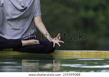 Yoga by the pool back into the wild. - stock photo