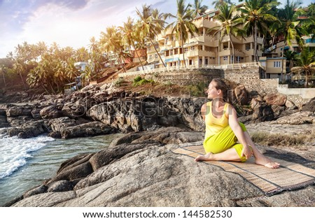 Yoga by woman in yellow costume on the stone nearby ocean and tropical resort in Kovalam, Kerala, India - stock photo
