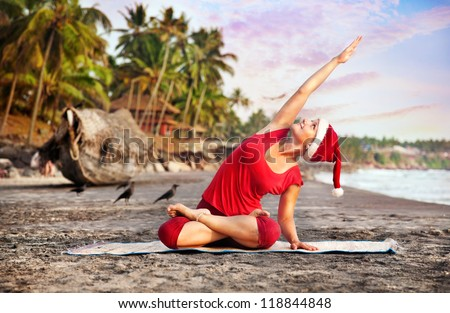 Yoga by young woman in red costume and red christmas hat on the beach near the ocean at tropic background in India - stock photo