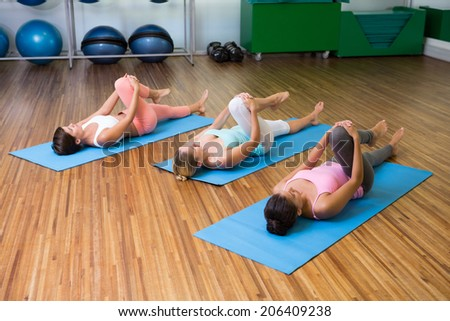 Yoga class stretching in fitness studio at the leisure center - stock photo
