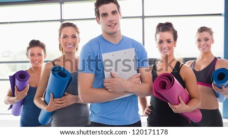 Yoga class with their trainer in gym - stock photo
