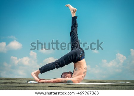 Yoga concept. Experienced yoga master performs various yoga poses on a roof over blue sky.