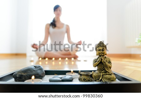 Yoga concept indoor. Woman meditating in lotus pose with buddha and candles on foreground. - stock photo