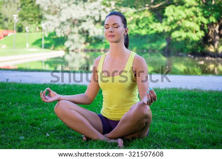 yoga concept - young sporty woman sitting in lotus pose in park