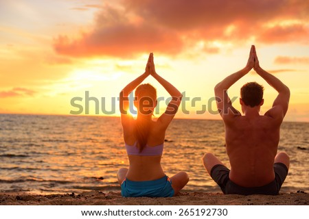 Yoga couple relaxing doing meditation on beach. Silhouettes of man and woman people practicing yoga pose sitting at a beach in the lotus position with their hands raised against a colorful sunset sky. - stock photo