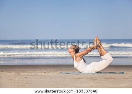 Yoga dhanurasana bow pose by woman in white costume on the beach near the ocean in Goa, India - stock photo