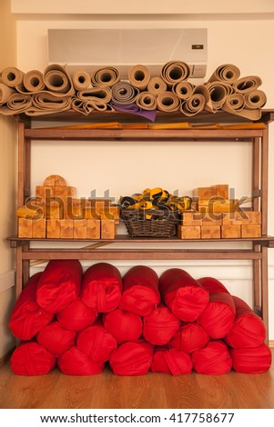 Yoga equipment. Mat, wooden blocks, pillow and strap on rack.