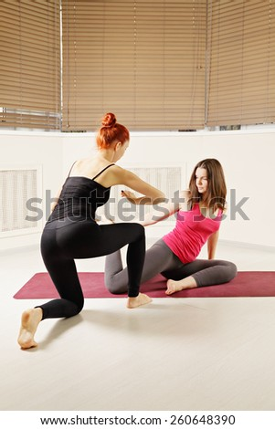 Yoga exercise in class redhead instructing brunette woman - stock photo