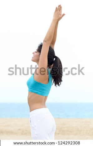 Yoga exercise on beach. Beautiful fitness woman meditating and breathing on summer morning. Caucasian brunette model outdoor. - stock photo