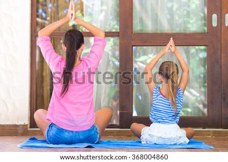 Yoga exercise on terrace by happy mom and girl in lotus position outdoors - stock photo