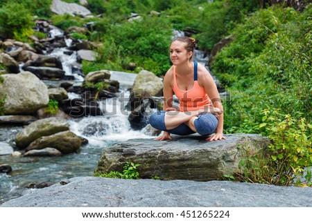 Yoga exercise outdoors -  woman doing Ashtanga Vinyasa Yoga arm balance strength training asana Tolasana - scales pose at waterfall in Himalayas - stock photo