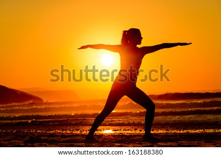 Yoga exercises in beach on beautiful summer sunset alone. Fit female silhouette relaxing, breathing and exercising. - stock photo