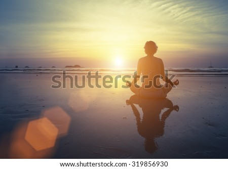 Yoga, fitness and healthy lifestyle. Silhouette meditation girl on the background of the stunning sea and sunset. Woman doing meditation near the ocean. Yoga silhouette. - stock photo