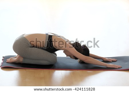 Yoga, fitness, sport, training and lifestyle concept - smiling woman stretching leg on mat in gym - stock photo
