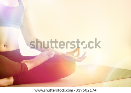 Yoga girl meditating indoor and making a zen symbol with her hand. Closeup of woman body in yoga pose Photo with color filters and warmth background. - stock photo