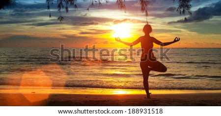 Yoga girl on the beach during sunset. - stock photo