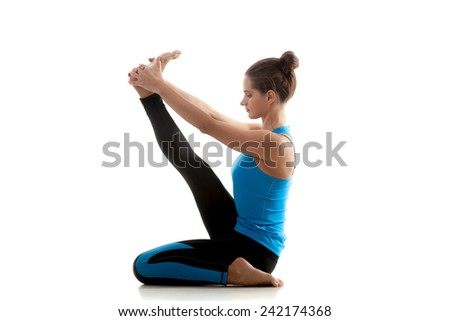 Yoga girl practices in black and blue sportswear on white background looks in front of her - stock photo