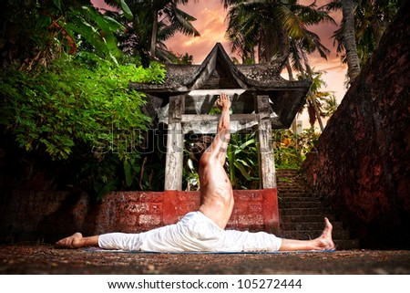 Yoga hanumanasana monkey pose by man in white trousers near stone temple in tropical forest - stock photo