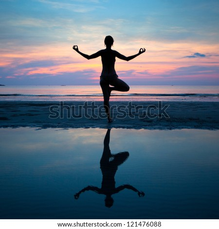 Yoga, harmony of health (silhouette young woman on the beach at sunset) - stock photo