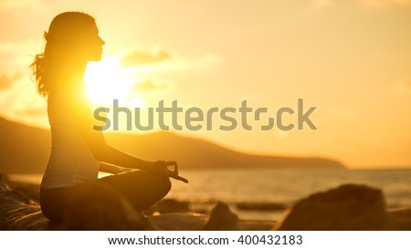 yoga in the beach. woman meditating in lotus pose at sunset