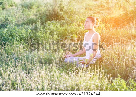 Yoga in the city: beautiful young fit woman wearing sportswear meditating, breathing, sitting with crossed legs in Half Lotus Posture on the street on summer day, Ardha Padmasana, copy space - stock photo